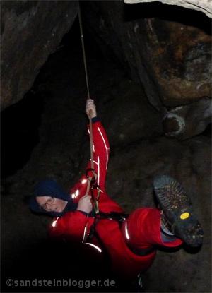 Ein Kletterer erkundet einen bislang unbekannten Höhlenzugang