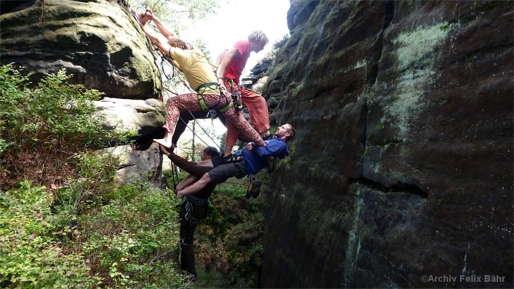 Kletterer bauen für eine Erstbegehung eine menschliche Brücke