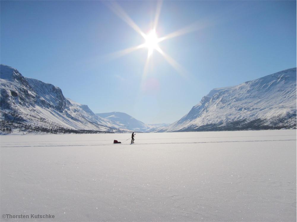 Einsamer Skifahrer vor verschneiter Bergkulisse