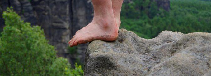 Füße an einer Felskante