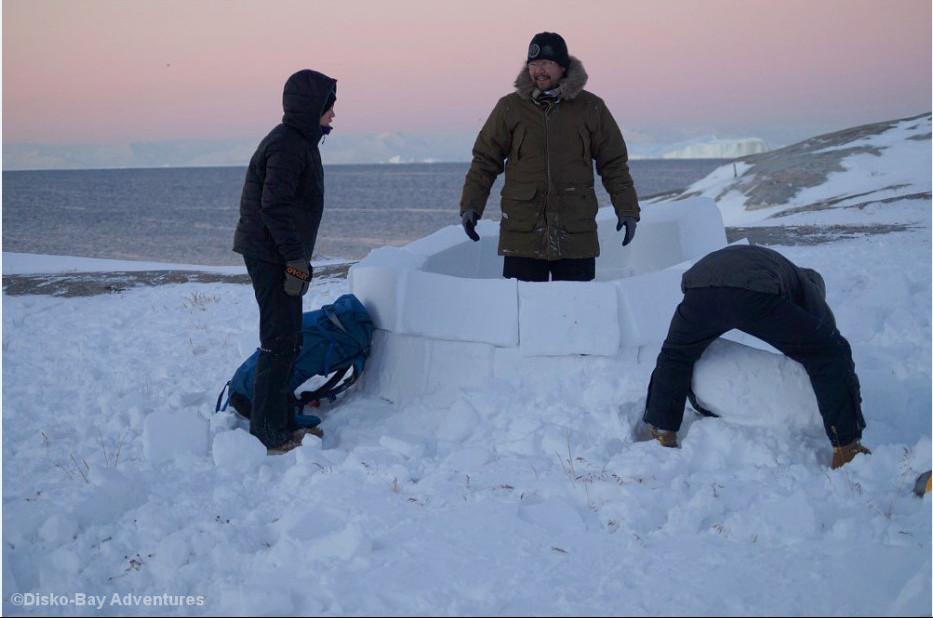 Drei Männer bauen ein Iglu