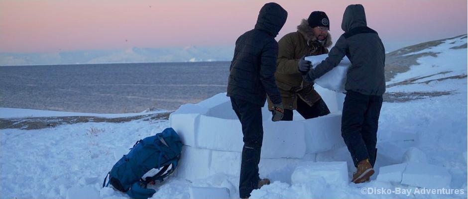 Drei Inuit bauen ein Iglu