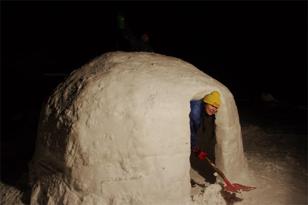 Frau schippt Schnee am Eingang des Iglus