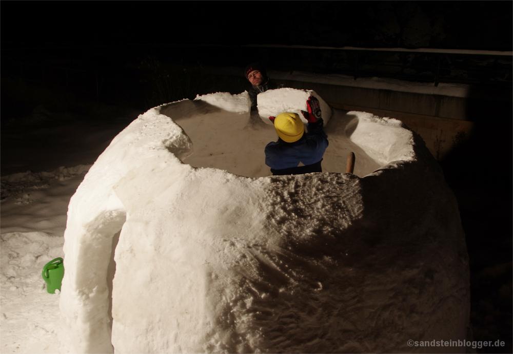 Mann und Frau bauen das Dach eines Iglus fertig