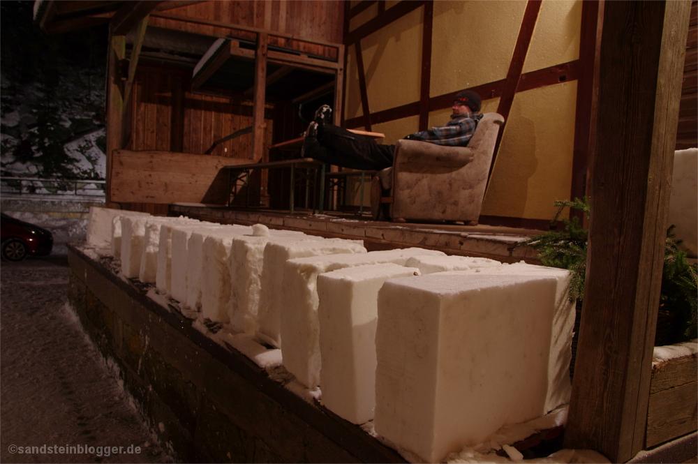 Die fertigen Eisblöcke auf der Laderampe der Buschmühle, dahinter Gastwirt im Sessel
