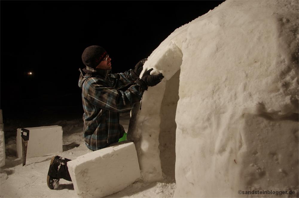 Mann verputzt den Eingang des Iglus mit Schnee