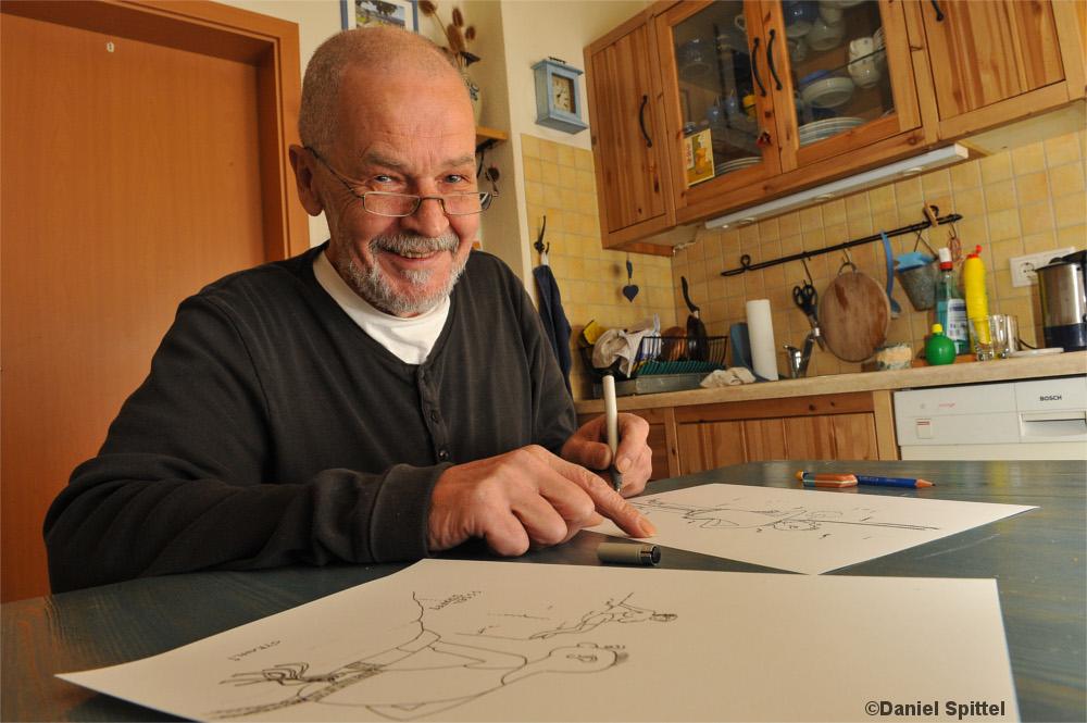Karikaturist Wolfgang Strahl beim Zeichnen am Küchentisch