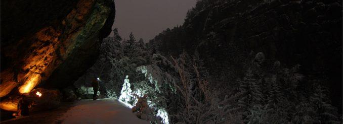Ein Mann mit Lampe unter einem Felsen - Nachthimmel, verschneiter Wald
