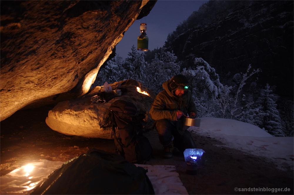 Mann mit Topf und Kocher unter Felsen, verschneiter Wald, Nacht