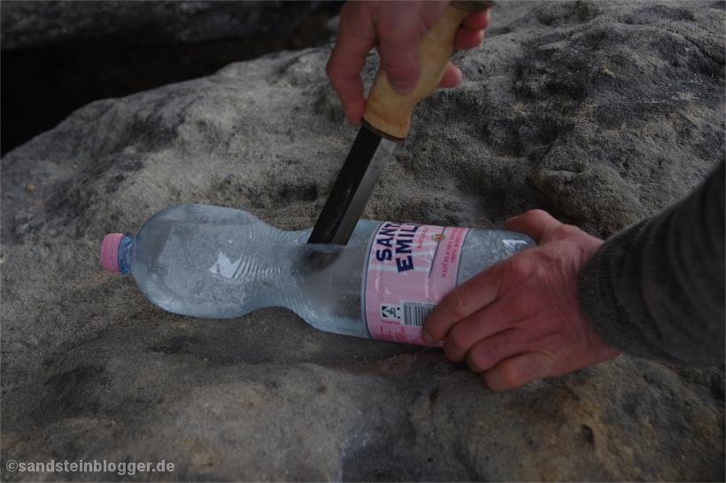 Plasteflasche wird mit Messer aufgeschnitten, gefrorenes Trinkwasser