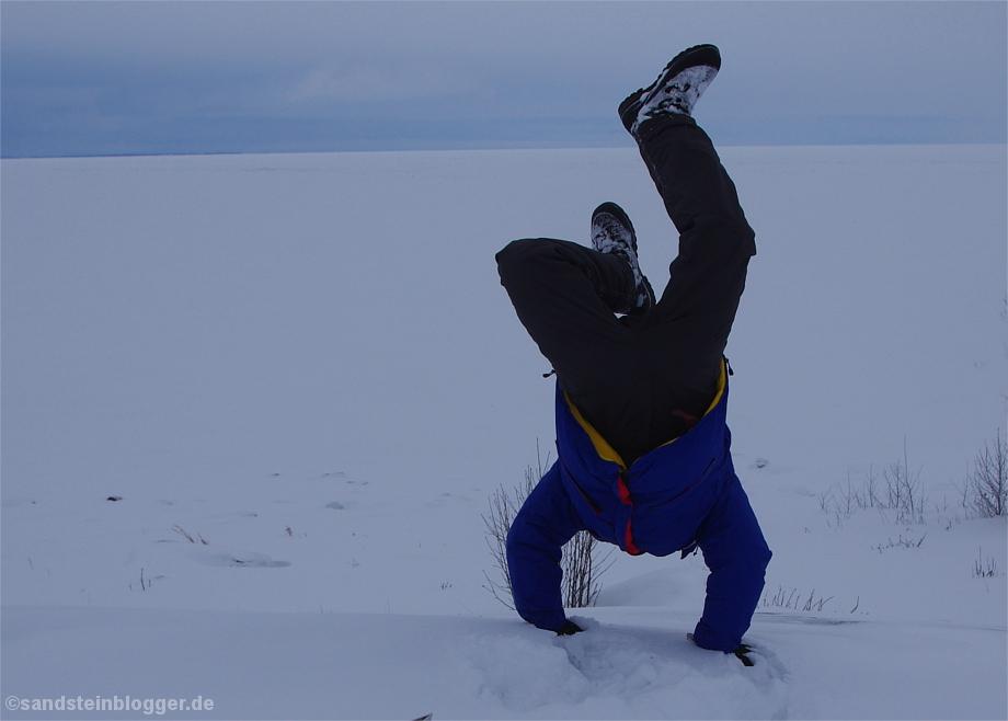 Mann macht Handstand im Schnee