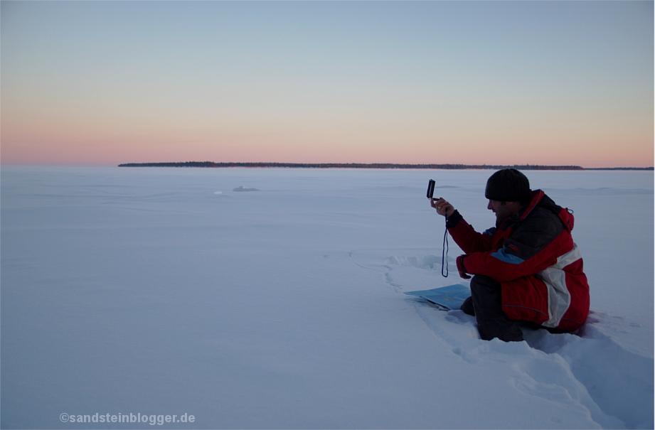 Mann mit Kompass im Schnee beim Anpeilen einer Insel