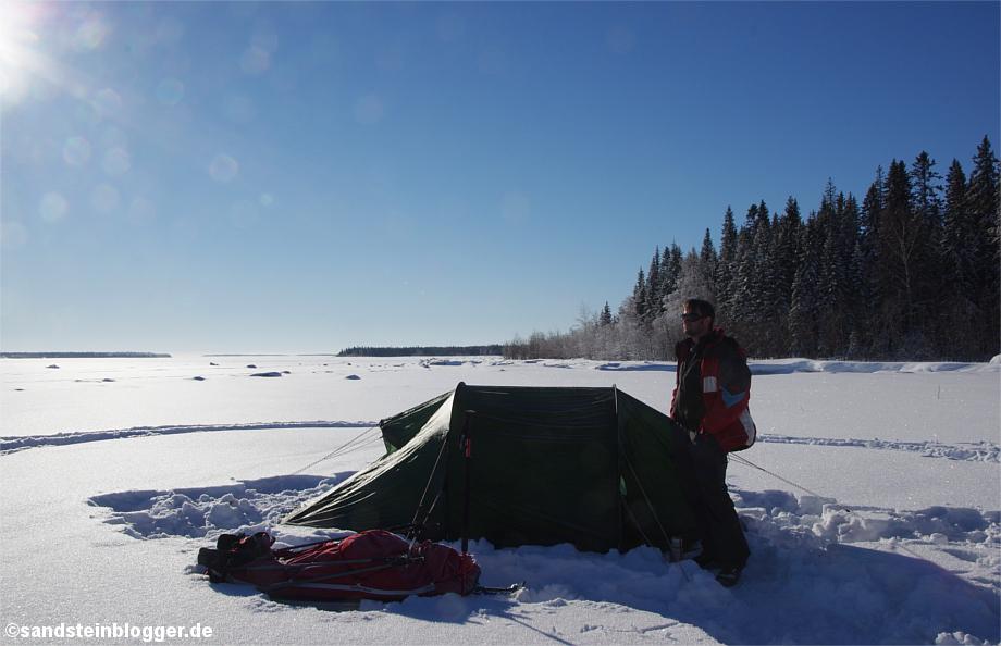 Mann mit Zelt in verschneiter Winterlandschaft