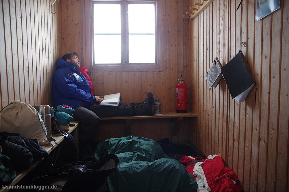 Mann in Daunenjacke in der Sauna