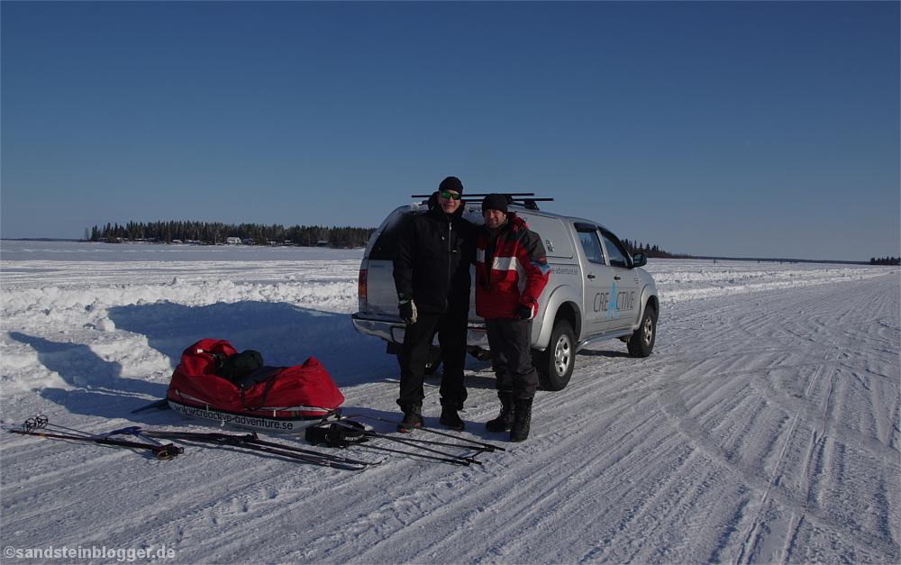 Zwei Männer und ein Geländewagen auf dem Eis, davor ein Pulka, Skier und Skistöcke im Schnee