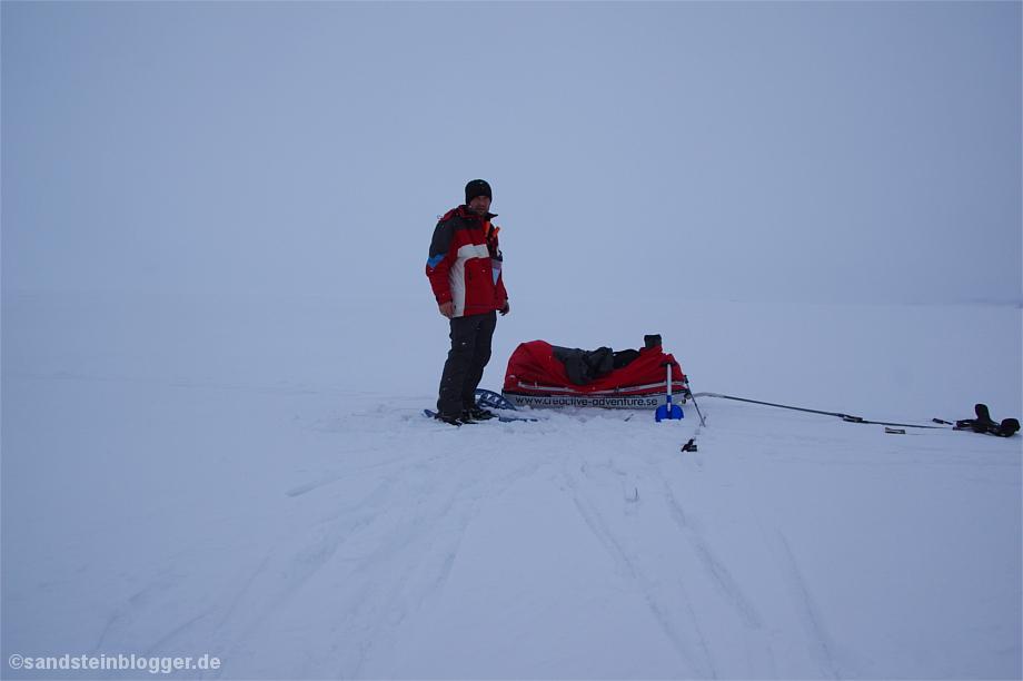 Mann mit Pulka im Schneetreiben
