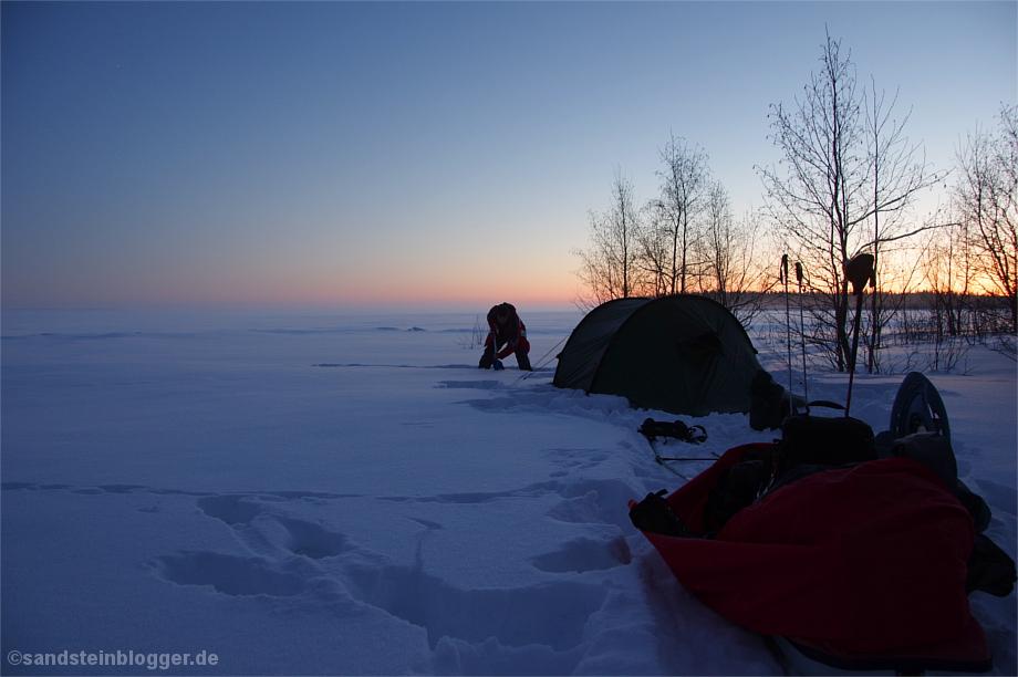Mann vergräbt Zeltheringe im Schnee
