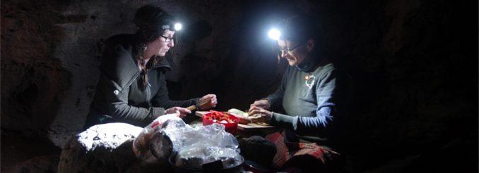 Zwei Frauen mit Stirnlampe schneiden Gemüse, dahinter Felsen