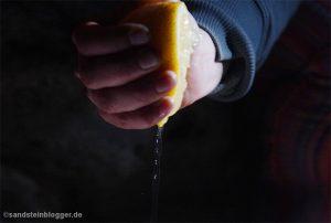 Hand quetscht Zitrone aus