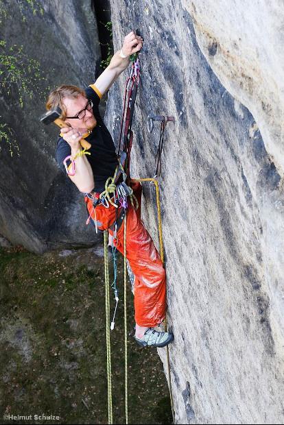 Kletterer schlägt einen Ring in den Fels
