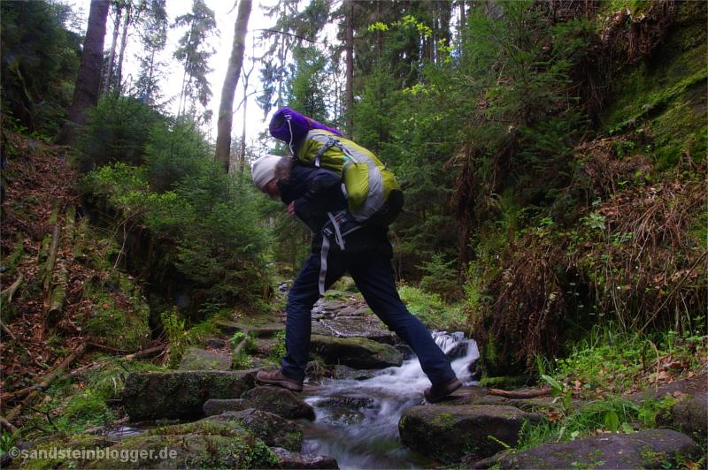 Trekkerin beim Überqueren eines Bachs