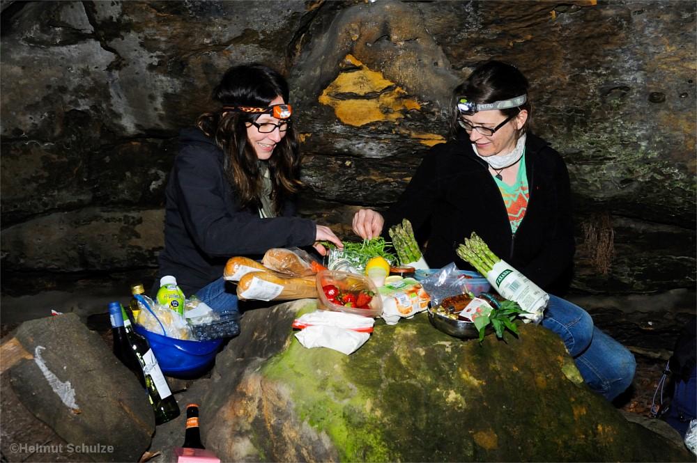 Zwei Frauen, die Spargel und Erdbeeren auf einem Felsblock sortieren.