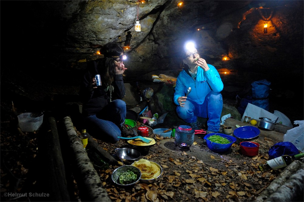 Frauen kochen unterm Felsüberhang