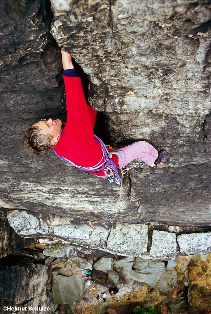 Mann beim Klettern an Felswand