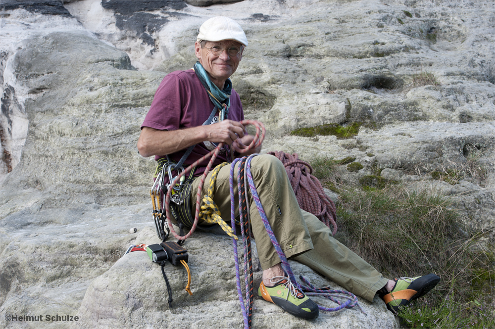 Kletterer mit Sschlingen und Karabiniern auf einem Felssockel