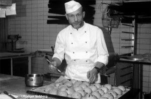 Bäcker mit Brötchenteig in seiner Backstube