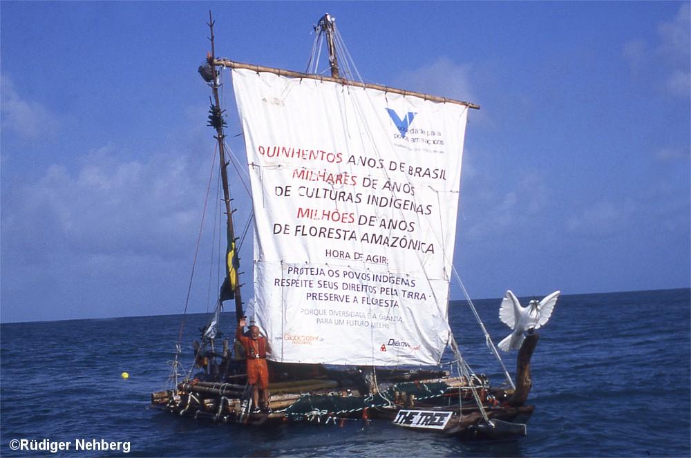 Baumstamm mit Segel auf hoher See, Skipper winkt in die Kamera