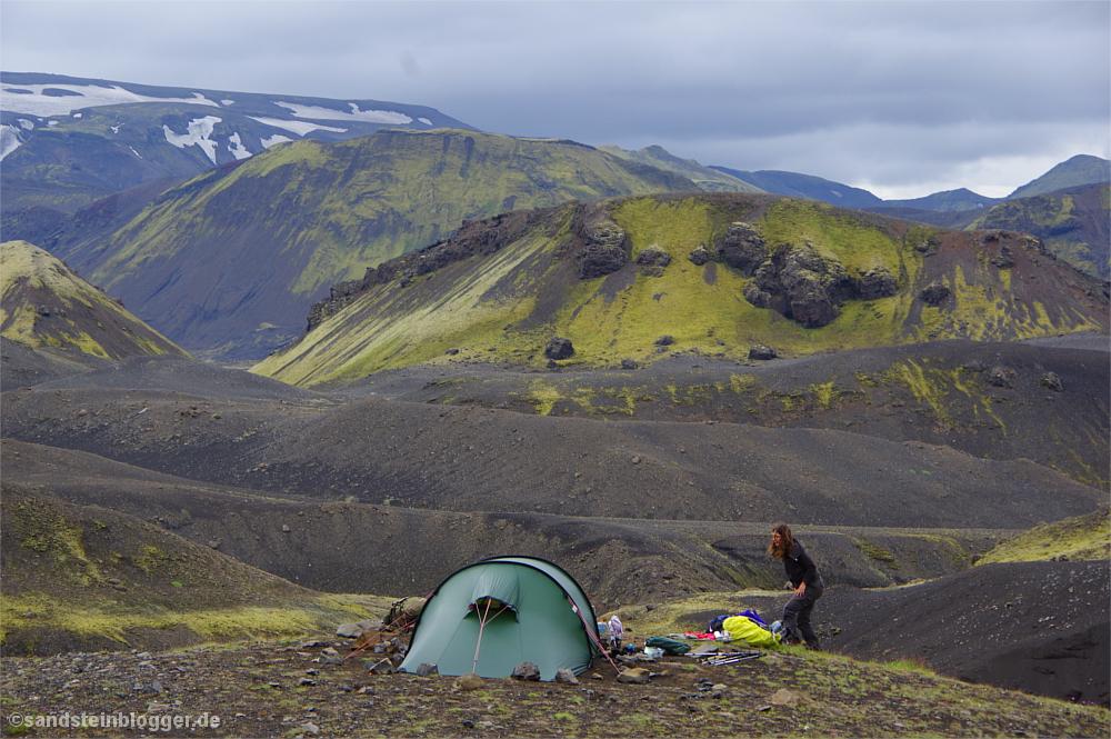 Zelt und Frau vor Bergkulisse