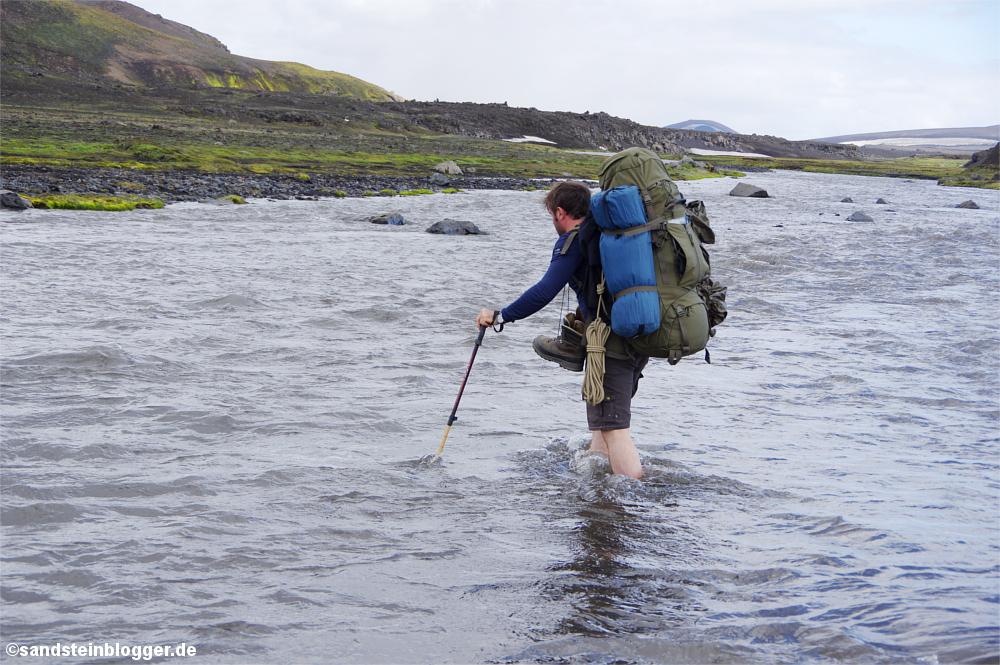 Mann watet mit Rucksack durch Fluss