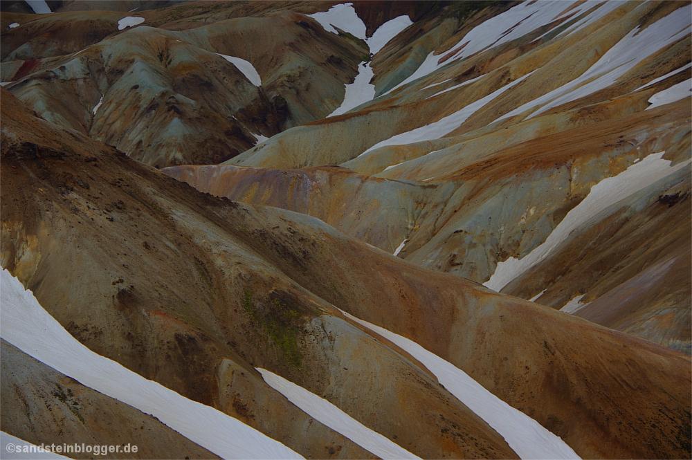 Berghänge aus buntem Stein mit Schnee