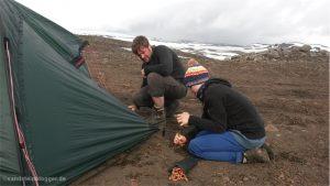 Mann und Junge bauen ein Zelt auf
