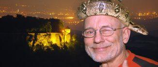 Survival-Künstler Rüdiger Nehberg mit einer Schlange auf dem Kopf vor der Silhouette der Festung Königstein