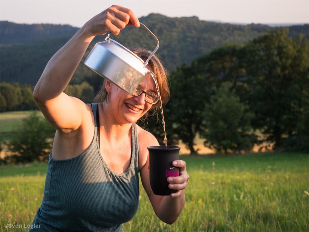 Frau schenkt sich einen Becher Wasser ein.