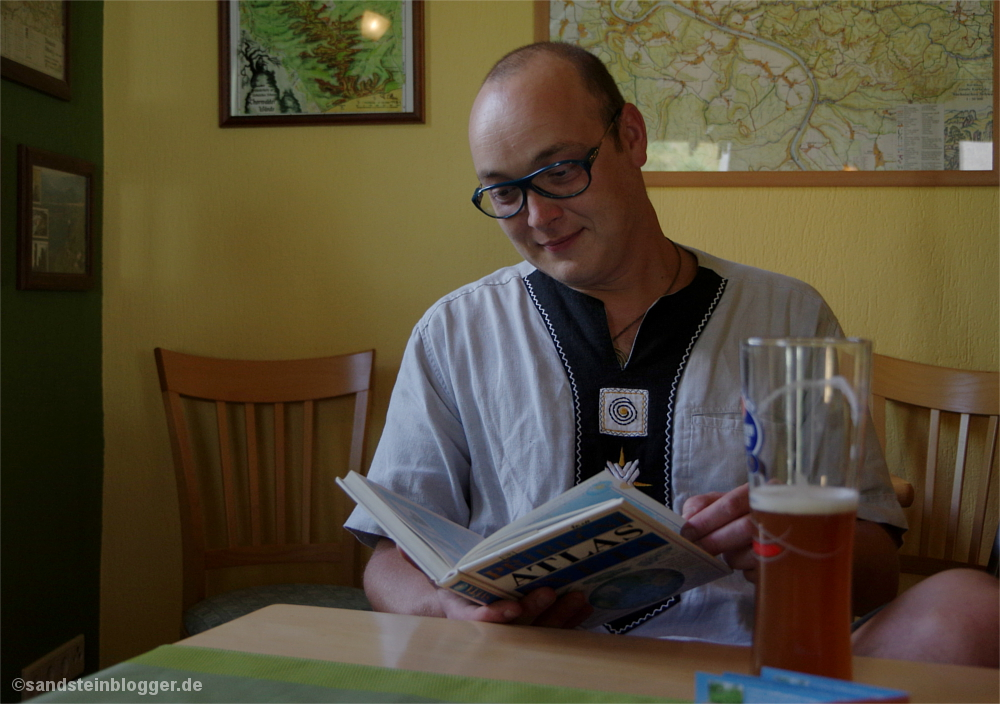 Mann mit Atlas in der Hand, im Vordergrund ein Bier.