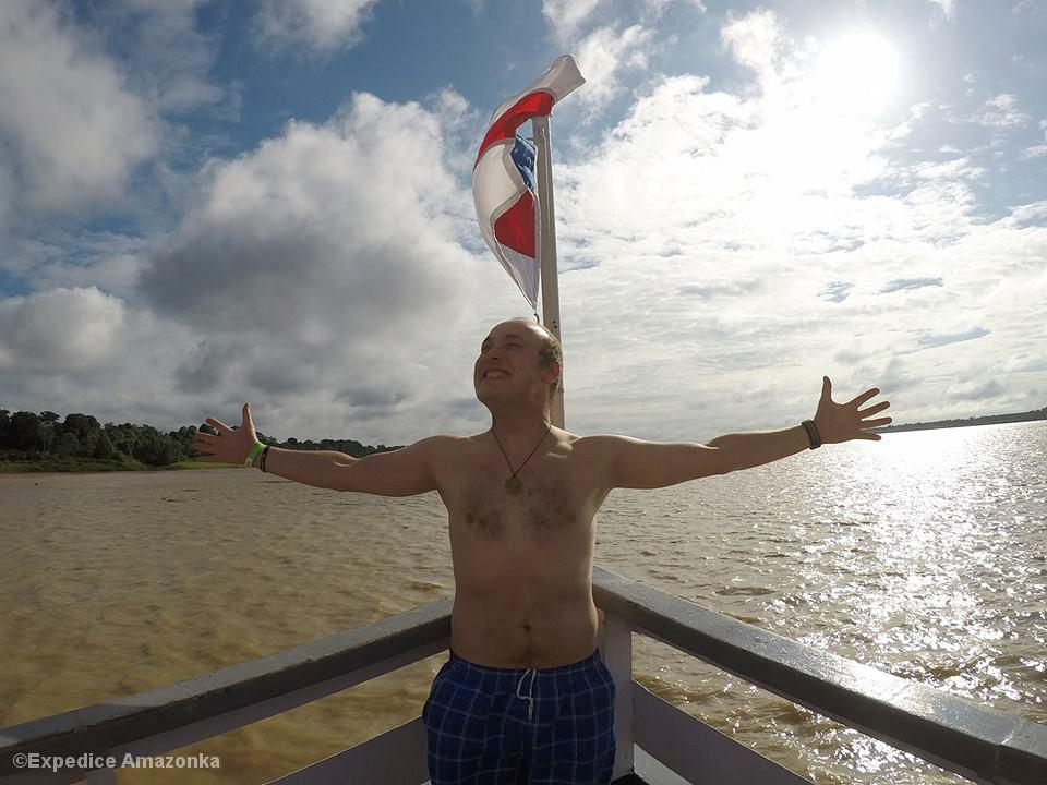 Mann mit nacktem Oberkörper und ausgebreiteten Armen am Bug eines Schiffs