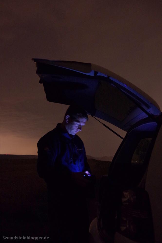 Mann am Auto mit Kamera
