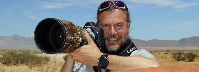 Mann mit Kamera vor Wüstenlandschaft