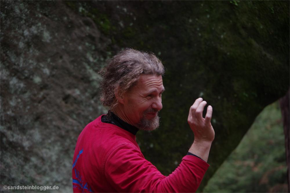 Mann gestikuliert vor einem Felsen