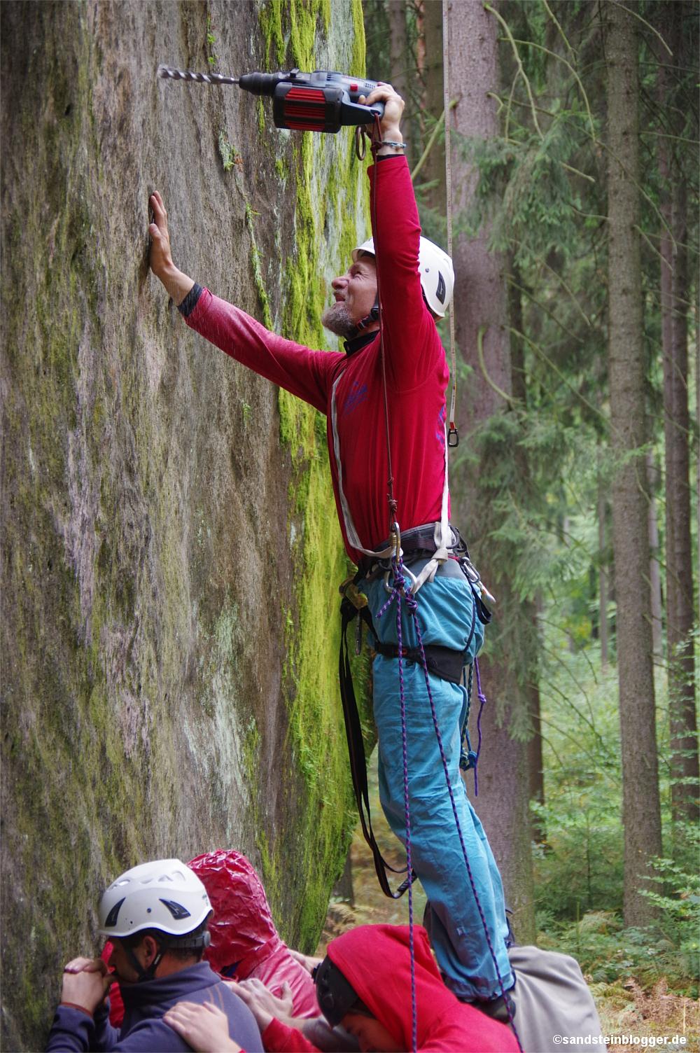 Mann bohrt ein Loch in die Felswand