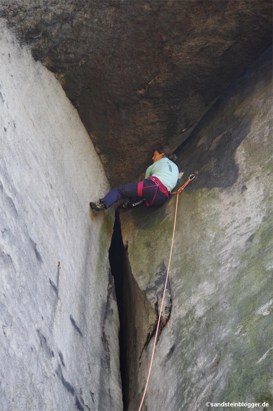 Frau klettert Felsriss