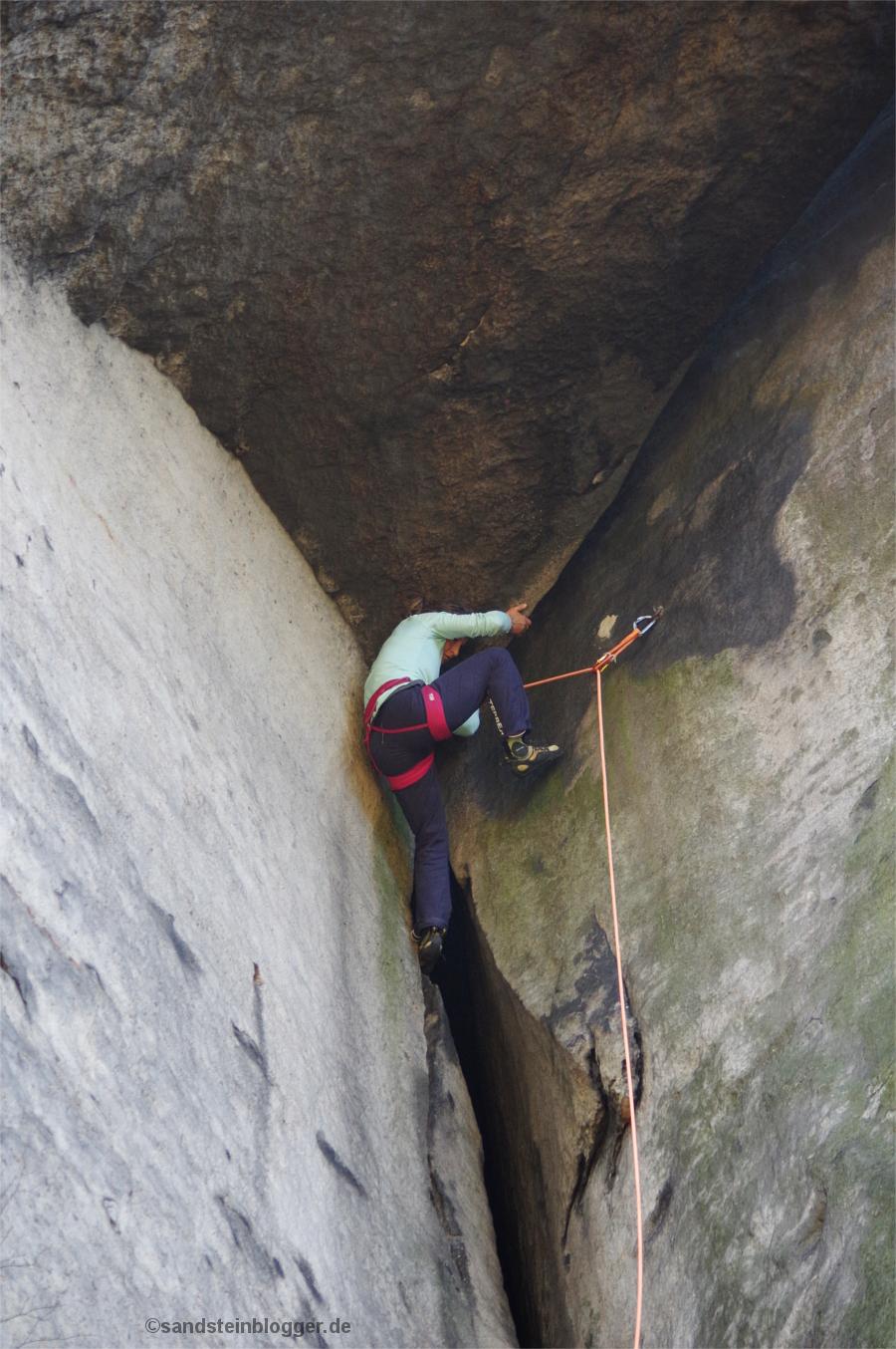 Frau hangelt an Felsdach