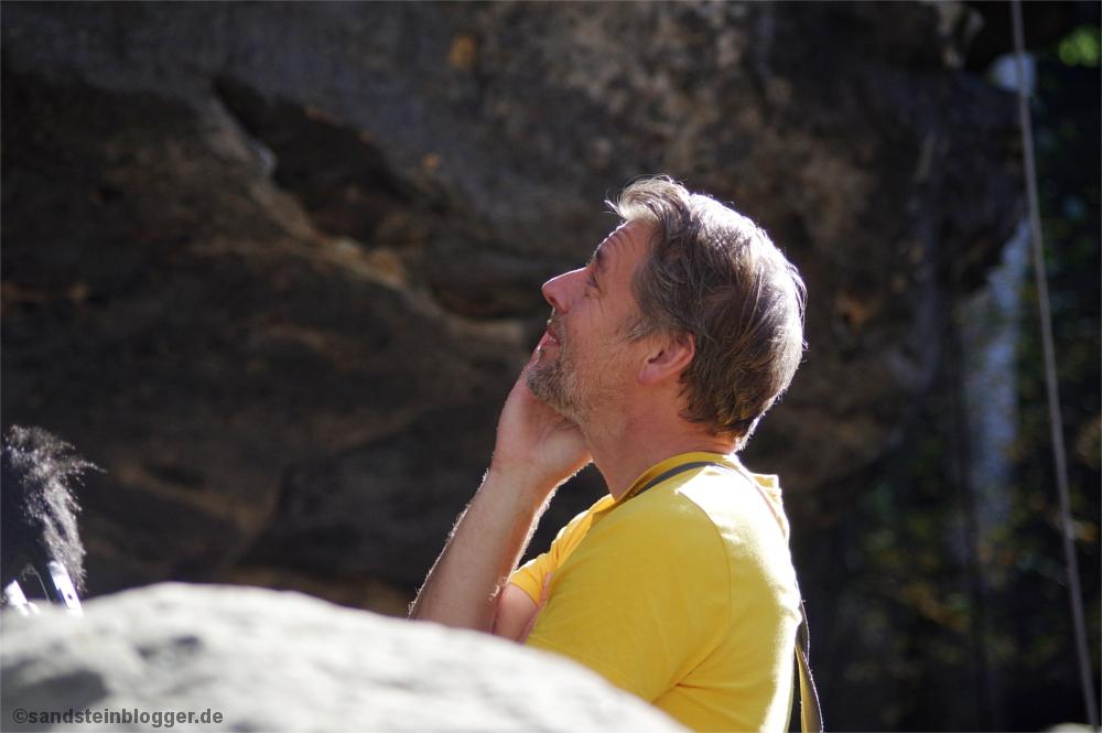 Mann guckt am Fels hoch