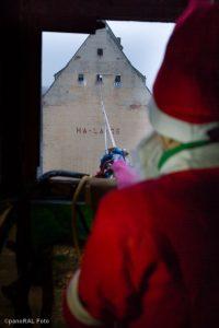 Weihnachtsmann vor Dachfenster, dahinter Hochseil