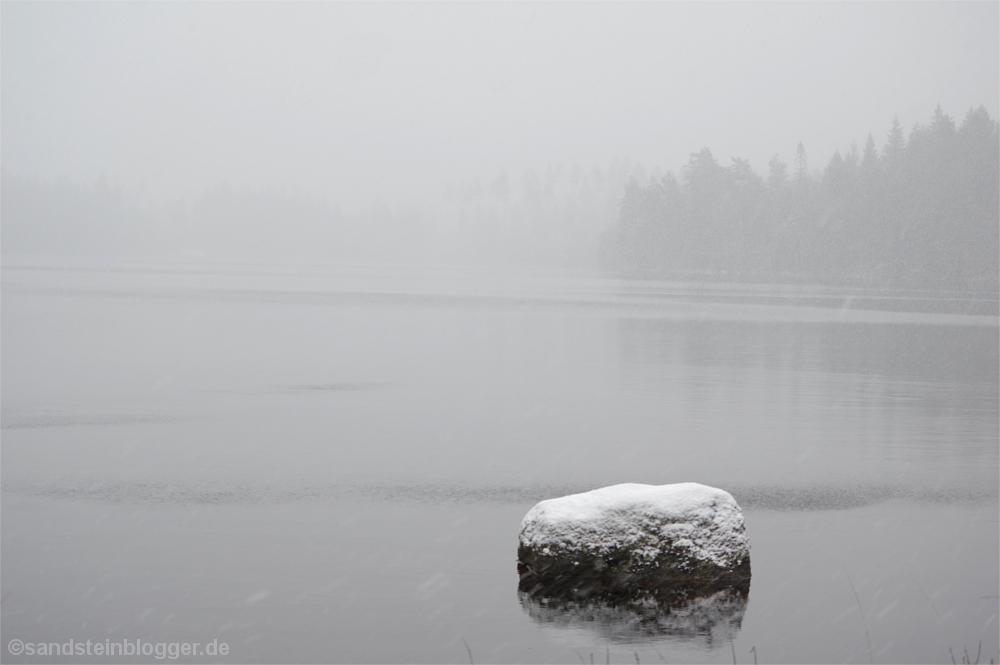 Verschneiter Stein im See