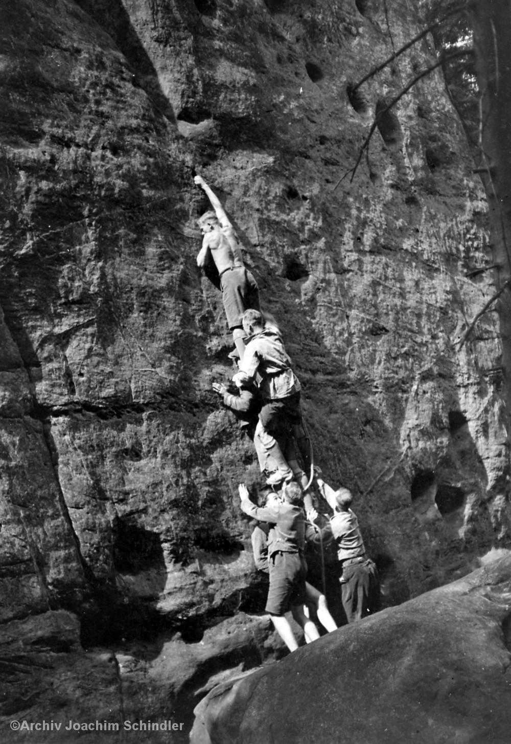 Kletterer bauen eine Menschenpyramide, um eine schwierige Stelle zu überwinden