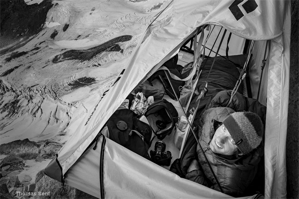 Mann imSchlafsack im Portaledge, neben ihm Kameras, Objektive und andere Fotoausrüstung